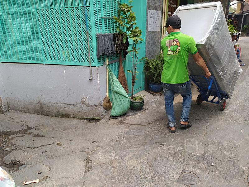 nhân viên Hailua Moving dùng xe đẩy kéo tủ lạnh vào hẻm nhỏ